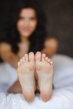 Härlig fot som ligger i sängen av en ung kvinna fotografering för bildbyråer