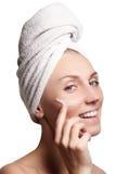 Härlig framsida av den unga kvinnan med cosmetickräm på en kind Begrepp för hudomsorg Closeupstående som isoleras på vit Närbild Royaltyfri Foto