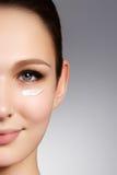 Härlig framsida av den unga kvinnan med cosmetickräm på en kind Sk arkivfoto