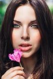Härlig framsida av den unga kvinnan med makeup över de rosa blommorna Stående av den nätta sunda hudflickan utomhus- royaltyfri foto