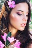 Härlig framsida av den unga kvinnan med makeup över de rosa blommorna Stående av den nätta sunda hudflickan utomhus- royaltyfri fotografi