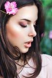 Härlig framsida av den unga kvinnan med makeup över de rosa blommorna Stående av den nätta sunda hudflickan utomhus- royaltyfri bild