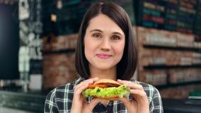 Härlig framsida av den vänliga unga flickan som poserar rymma den nya saftiga hamburgaren som ser kameran arkivfilmer
