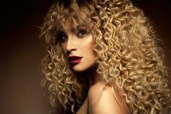 Härlig framsida av en modemodell med blåa ögon lockigt hår röda kanter arkivfoton
