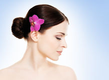 Härlig framsida av en ung och sund flicka med en orkidéblomma i hennes hår Fotografering för Bildbyråer