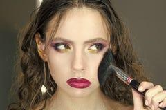 Härlig framsida och makeover perfekt hud applicera makeup Skönhetflicka med makeupborsten Ljust feriesmink för arkivbilder