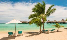 Härlig fransk Polynesian strand med stolar och paraplyet Avkoppling- och semesterbegrepp arkivbilder
