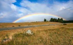 Härlig full dubbel regnbåge över vägen Royaltyfri Bild