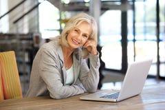 Härlig funktionsduglig bärbar datordator för äldre kvinna inomhus royaltyfria bilder