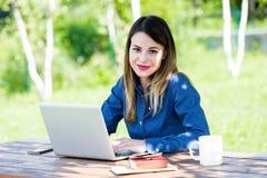 Härlig funktionsduglig det fria för flickastudent på bärbara datorn royaltyfria bilder