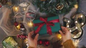 Härlig gåva i händerna av män Nytt års gåva med ett rött band, gran på tabellen Mannen gjorde det själv och är stock video