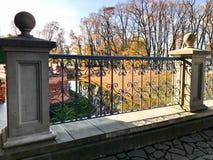 Härlig gammal forntida tappning stenar smidesjärnräcket av en bro med modeller på bakgrunden av floden och träden royaltyfria foton