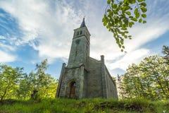Härlig gammal kyrka och i träden Arkivfoto