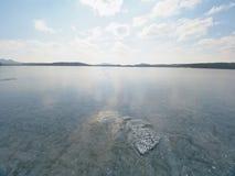 Härlig genomskinlig styckis av sjön mot himmel och den ljusa solen Arkivbilder