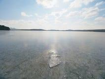 Härlig genomskinlig styckis av sjön mot himmel och den ljusa solen Arkivbild
