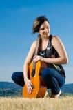 härlig gitarrist som poserar utomhus arkivbild