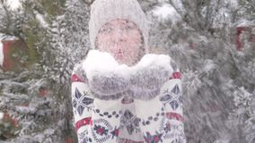 Härlig glad kvinna som har gyckel i vintern som blåser snöultrarapid 180fps arkivfilmer