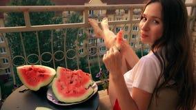 Härlig gladlynt brunettkvinna som äter vattenmelon på en terrass lager videofilmer