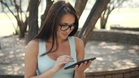 Härlig gladlynt flicka med en minnestavlaPC som sitter i en parkera på en bänk på en Sunny Day, on-line shoppingbegrepp Royaltyfria Foton