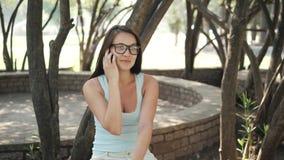 Härlig gladlynt flicka med ett Smartphone sammanträde i en parkera på en bänk på en Sunny Day Fotografering för Bildbyråer