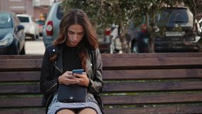 Härlig gladlynt flicka med ett smartphonesammanträde i en parkera på en bänk på en tonåring för solig dag, online-shoppingbegrepp lager videofilmer