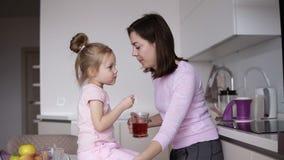 Härlig gladlynt mum med brunetthår och hennes lilla lilla dotter som kysser sig, medan flickan sitter på stock video