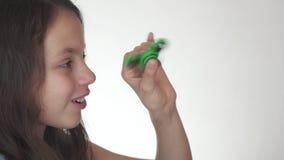 Härlig gladlynt tonårig flicka som spelar med den gröna rastlös människaspinnaren på den vita videoen för bakgrundsmateriellängd  lager videofilmer