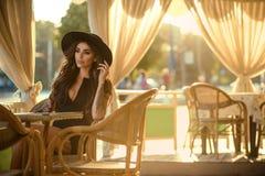 Härlig glam tatuerade brunett i liten svart klänning och moderiktigt fedorahattsammanträde i den trevliga sommarrestaurangen för  royaltyfri fotografi