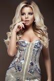 Härlig glamourblondiekvinna i elegant klänning med juvlar, aftonmakeup och krullning Skönheten av framsidan Royaltyfri Bild