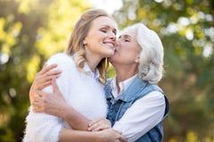 Härlig grå haired kvinna som kysser hennes dotter i kinden Arkivfoton