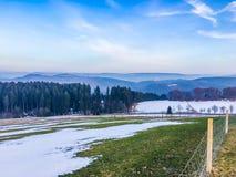 Härlig grön bygdlandskapplats med smältande snö och sikt på bergkullarna som göras i Tyskland Hochsauerland royaltyfri foto