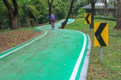 Härlig grön cykelgränd med roadsign i parkera Arkivfoto