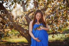 Härlig gravid kvinna i den oavkortade growten för frodig vårträdgård Royaltyfria Bilder