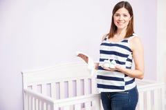 Härlig gravid kvinna i en barnkammare Arkivfoto