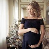 Härlig gravid kvinna i en ferieklänning arkivfoto