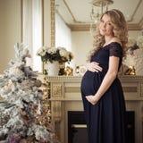 Härlig gravid kvinna i en ferieklänning fotografering för bildbyråer