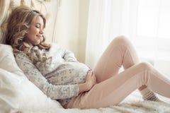Härlig gravid kvinna i hemtrevlig kläder arkivfoto