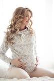 Härlig gravid kvinna i hemtrevlig kläder arkivbilder