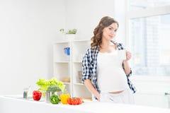 Härlig gravid kvinna i köket med det shoppingpåsen och äpplet Fotografering för Bildbyråer