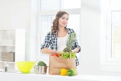 Härlig gravid kvinna i köket med shoppingpåsen och ananas Arkivfoto