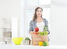 Härlig gravid kvinna i köket med shoppingpåsen och peppar Arkivfoton