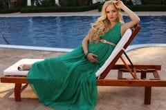 Härlig gravid kvinna med blont hår i elegant klänning Royaltyfri Foto