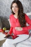 Härlig gravid kvinna med en minnestavla i händer Royaltyfria Foton