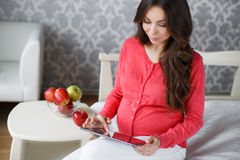 Härlig gravid kvinna med en minnestavla i händer Arkivfoto