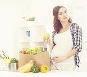 Härlig gravid kvinna med shoppingpåsar i kök Motherho Arkivbild
