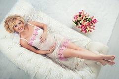 Härlig gravid kvinna med svart ligga för lyxigt hår på soffan Top beskådar Royaltyfria Bilder