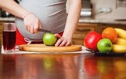 Härlig gravid kvinna på kök arkivfoton