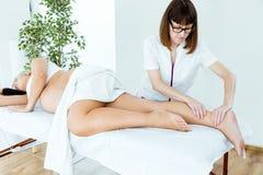 Härlig gravid kvinna som har en massage i brunnsort Arkivfoto