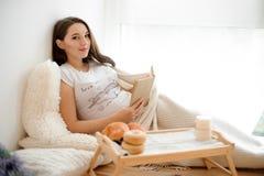 Härlig gravid kvinna som ligger på den vita sängen med en bok arkivfoton