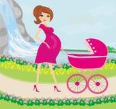Härlig gravid kvinna som skjuter en sittvagn med hennes dotter Arkivfoto